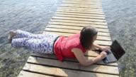 MS Woman using Laptop on jetty at Beach / Betina, Dalmatia, Croatia