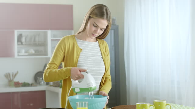 Woman using mixer in kitchen
