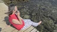 MS Woman using mobile phone on jetty at Beach / Betina, Dalmatia, Croatia