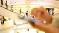 Woman Using Mobile Smart Phone in Shopping Mall