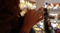 Frau mit Mobile Smartphone in Einkaufszentrum