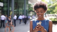 Woman using phone, smiling, in busy area.