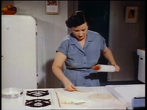 1950 woman using rolling pin on dough (making shortcake) on counter in kitchen