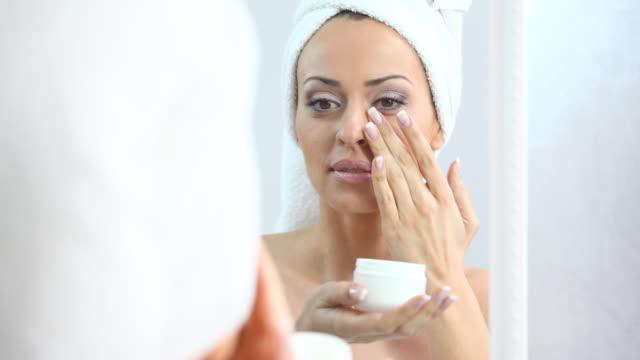 Woman using skin moisturizer.