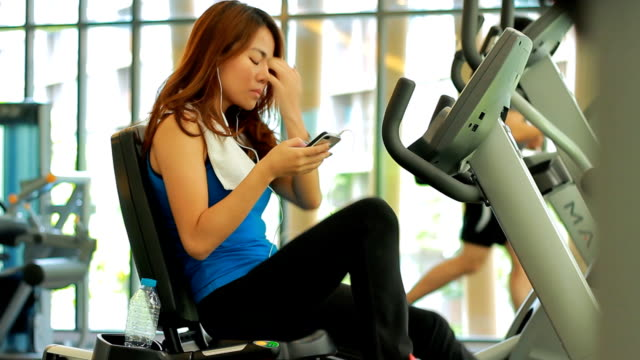 Woman using smart phone at gym