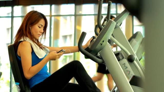 Frau mit Smartphone im Fitnessraum