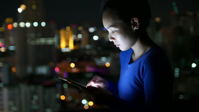Woman using smart phone at night and Bokeh of City on Top roof of Hotel