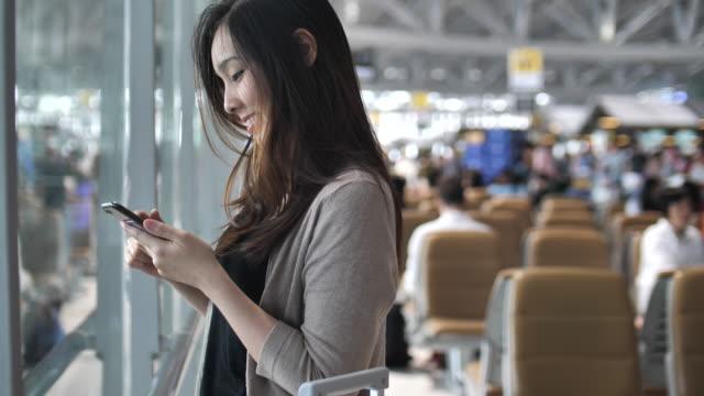 Frau mit Smartphone im Flughafen