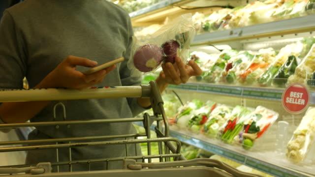 Frau mit Smartphone im Supermarkt