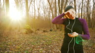 Woman using smart phone while jogging.