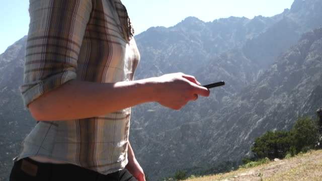 Woman using smartphone in mountain range