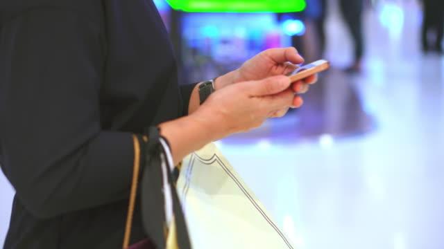 Kvinna med smartphone i köpcentrum