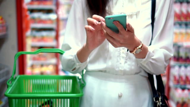 Woman using smartphone in supermarket,Slow motion