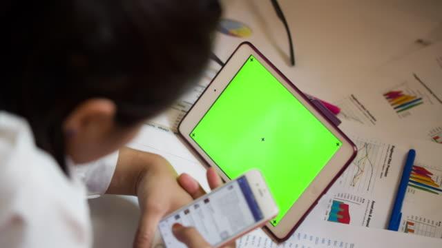 Kvinna med smartphone med tablett grön skärm blank