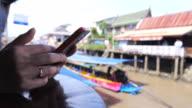Kvinna med surfplatta på Amphawa Floating Market traditionella Resor Thailand