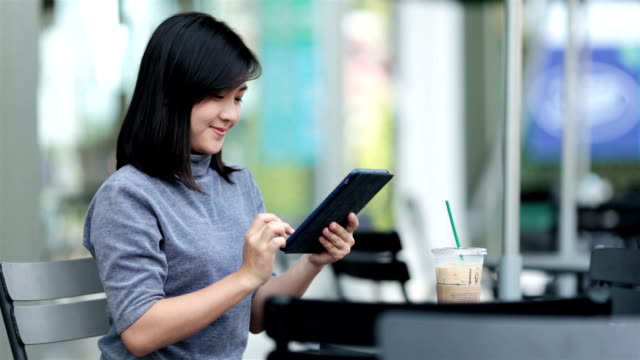 Woman using tablet in a coffee shop