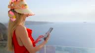 Woman using tablet on terrace & seascape