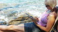 HD DOLLY: Woman Using Tablet On The Beach