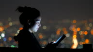Vrouw die tablet pc gebruikt in de nacht met bokeh achtergrond