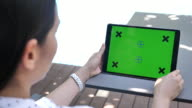 Woman using Tablet PC with Green screen, Horizontal