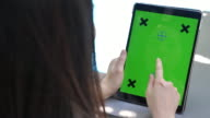 Woman using Tablet PC with Green screen, vertical