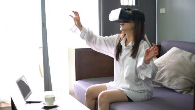 Woman using virtual reality glasses at home