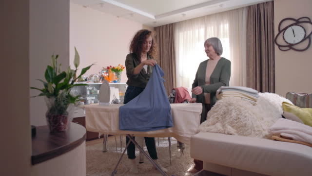 Woman volunteer ironing clothes for senior woman