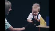 VS Woman w/ puppet playing peekaboo w/ toddler at geometric block table LA Boy child blocks falling calling out smiling VS Children toddler talking...