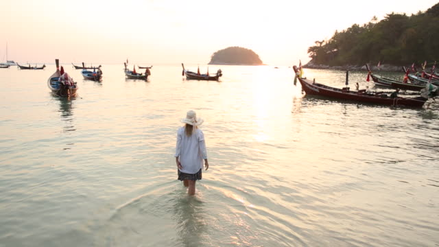 Woman wades into tropical sea, looks towards sunrise