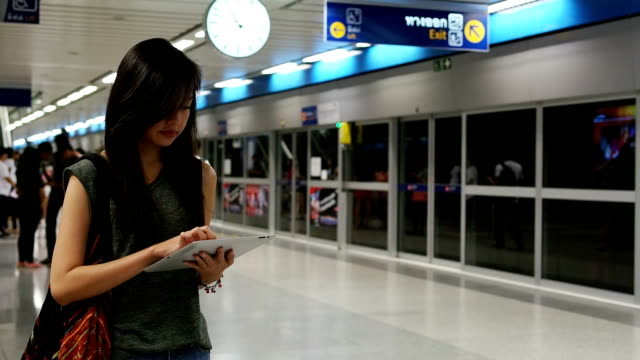 Woman waiting for train looking at digital tablet