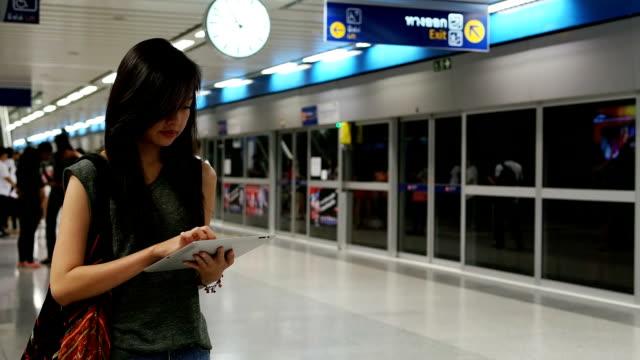 Donna in attesa del treno alla ricerca su tablet digitale