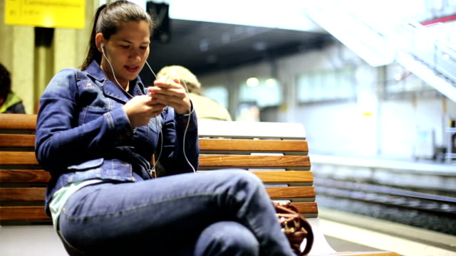 Woman waiting for train looking at smartphone