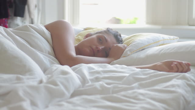 Woman waking up in white bed in bedroom