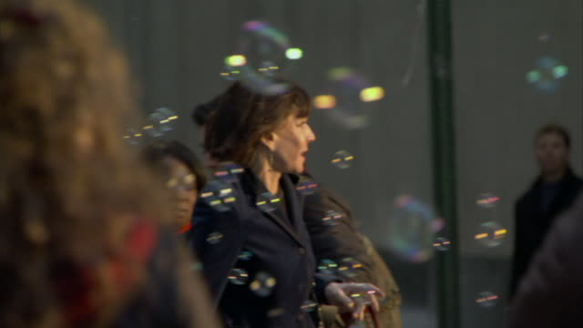 MS PAN Woman walking across street while bubbles float in air / Manhattan, New York, USA
