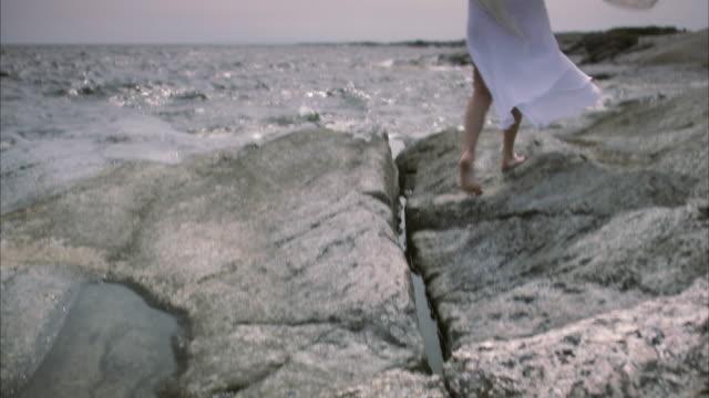 A woman walking along a rocky shore Huvudskar Stockholm archipelago Sweden.