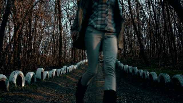 Woman walking along Forest footpath marked with old painted car tires