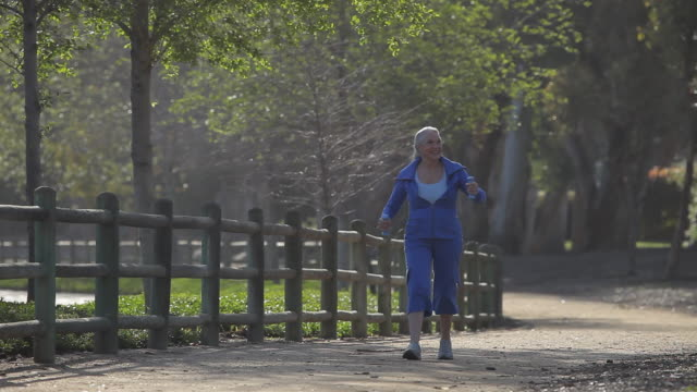 WS PAN Woman walking and doing arm exercise with small weights / Los Angeles, California, USA