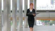 Donna a piedi e tenendo una cartella