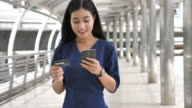 Woman walking and online shopping on Mobile phone, Slow motion
