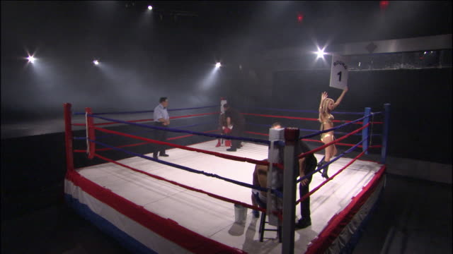 HA WS Woman walking around boxing ring with Round 1 sign while trainers talk to boxers in ring corners / Jacksonville, Florida, USA