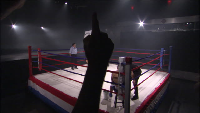 HA WS Woman walking around boxing ring with Round 7 sign while spectators applaud and trainers talk to boxers in ring corners / Jacksonville, Florida, USA