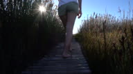 Woman walking at sunset on wooden footpath