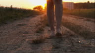 Woman walking barefoot on a dirt road