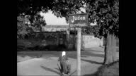 Woman walking by antiSemitic sign CU Same antiSemitic sign w/ swastika People in public park woman smiling at child CU Sign on yellow bench...