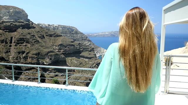 Woman walking by luxury pool