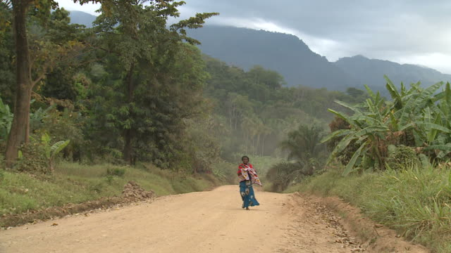 woman walking down a lonely dirt road in africa