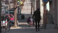 Woman walking down a street in the Bronx near 178th street with parked cars, a man sweeing the street, and other pedestrians during the day