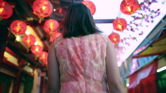 TS Woman walking down a street, under red lanterns