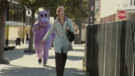 MS, DS, Woman walking down street being chased by person in purple hippo suit, Dallas, Texas, USA
