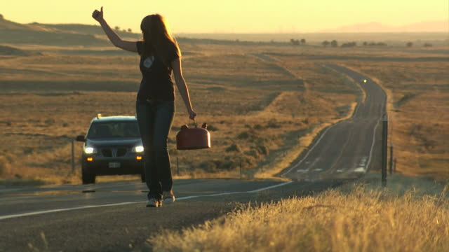 woman walking down the road with a gas can